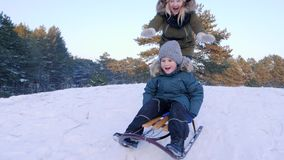Happy childhood, mother pushes son on sledge and he riding from hill in winter forest in slow motion. Happy childhood, mother pushes son on sledge and he riding stock footage