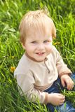 Happy childhood outdoor, little blond boy in green grass royalty free stock photo