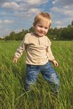Happy childhood outdoor, little blond boy in green grass stock images