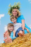 Happy childhood and parenting. Happy mother with children in summer at field and straw haystack Stock Photo