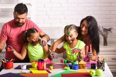 Happy childhood and parenting concept. Children playing and learning with parents. Family smiling with hands colored in paints. Arts and crafts. Girls drawing royalty free stock images