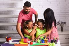 Happy childhood and parenting. Finger painting and arts. Imagination, creativity concept. Girls drawing with mother and father. Children playing and learning royalty free stock image