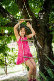 Happy childhood - playing child. Happy child is playing on rope ladder outside in nature Royalty Free Stock Image