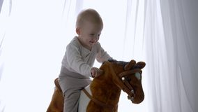 Happy childhood, smiling baby seating and swinging on toy horse at home. Close-up stock video