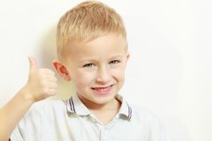Happy childhood. Smiling blond boy child kid showing thumb up stock photo
