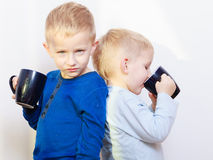 Happy childhood. Two brothers little boys drinking tea. Happy childhood. Two brothers funny little boys children kids standing back to back drinking tea. Sibling Royalty Free Stock Photos