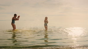 Happy childhood - two girls playing in the water. Laughing stock footage