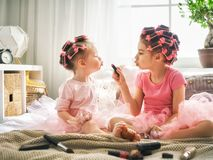 Sisters are doing hair and having fun. Happy childhood. Two sisters are doing hair and having fun. Children doing makeup sitting on the bed in the bedroom royalty free stock photography