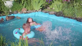 Two small children swim in a small pond. Brother and sister laughing, splashing water. Children swim on a hot summer day. Happy childhood. Two small children stock video