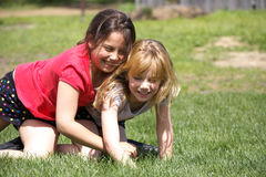 Happy children. Two little girls having fun wrestling in the green grass royalty free stock photography