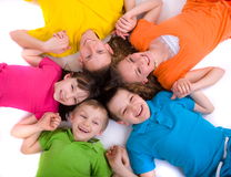 Happy children. Five caucasian happy smiling children lying in a circle on the floor and holding hands
