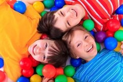 Happy Children. Lying in between colorful plastic balls royalty free stock photos
