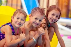 Happy children in aqua park. Portrait of a cute happy children having fun in aqua park, joyful siblings with pleasure spending summer holidays on the beach Royalty Free Stock Photo
