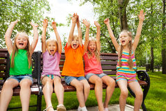 Happy children with arms and sit in row on bench. Happy excited group of children hold arms up straight in the air and sit in row on the bench stock photos