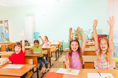 Happy children with arms up sitting in classroom. Happy large group of children with arms up sitting in classroom rows and smile in school Royalty Free Stock Image