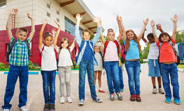 Happy children with arms up standing near school Royalty Free Stock Photo