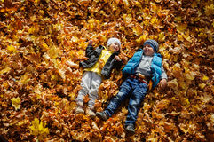 Happy children in autumn park lying on leaves Royalty Free Stock Image