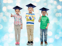 Happy children in bachelor hats and eyeglasses Royalty Free Stock Photos