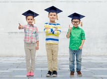 Happy children in bachelor hats and eyeglasses Stock Image
