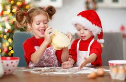 Happy children bake christmas cookies. Happy funny children bake christmas cookies stock photography