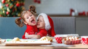 Happy children bake christmas cookies. Happy funny children bake christmas cookies stock photos