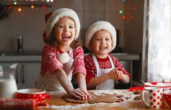 Happy children bake christmas cookies. Happy funny children bake christmas cookies Royalty Free Stock Images