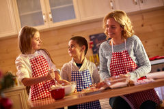 Happy children baking cookies with mother at home Royalty Free Stock Photo