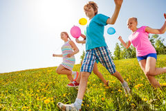 Happy children with balloons run in green field Stock Images