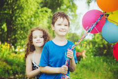 Happy children with balloons at summer park. Happy family concep Stock Images