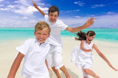 Happy children on beach. Three happy young children running and jumping on sandy tropical beach with sea and cloudscape in background Stock Images