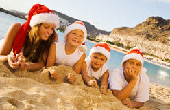 Happy children on the beach with christmas hats Royalty Free Stock Image