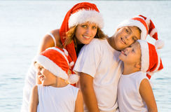 Happy children on the beach with christmas hats Royalty Free Stock Photo