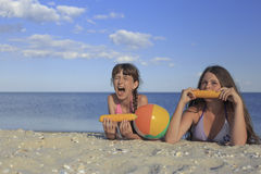 Happy children on the beach eating sweet corn. Stock Image