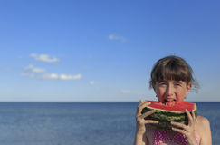 Happy children on the beach eating sweet watermelon. Stock Photo