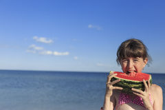 Happy children on the beach eating sweet watermelon. Royalty Free Stock Photos