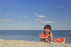 Happy children on the beach eating sweet watermelon. Stock Photography