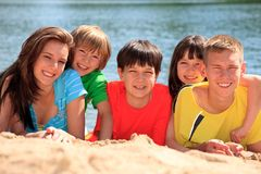 Happy children on beach sand. Happy smiling excited children at a sandy lake beach on a summer day stock photo