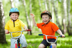 Happy children on bicycle on green park Royalty Free Stock Image