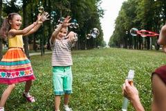 Happy children blows bubbles park concept. Happy children blows bubbles park family concept. Family values. Active leisure Stock Image