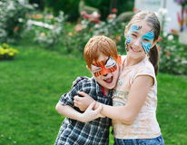 Happy children, boy and girl with face paint in park. Happy children with face art paint in park. Boy and girl outdoors on child birthday masquerade party have stock photography