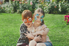 Happy children, boy and girl with face paint in park. Happy children with face art paint in park. Boy and girl outdoors on child birthday masquerade party have Stock Images