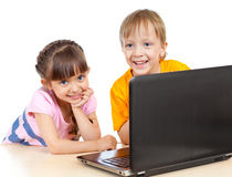 Happy children boy and girl using a laptop Royalty Free Stock Images