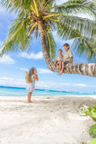 Happy children - boy and girls - on palm tree, tropical Stock Photos