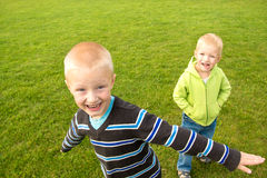 Happy children (boys, brothers) playing on green grass Royalty Free Stock Photography
