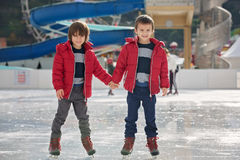 Happy children, boys, brothers with red jackets, skating during stock photography