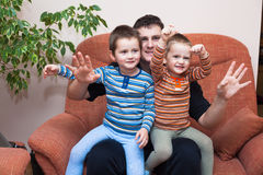 Happy children boys with daddy on sofa Stock Images