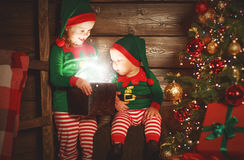 Happy children brother and sister elf, helper of Santa with Chri. Happy children brother and sister elf, helper of Santa with a Christmas magic gifts Stock Photography