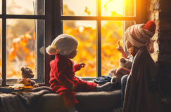 Happy children brother and sister looking through windows in fal. Happy children brother and sister looking through the windows in the fall Royalty Free Stock Photo