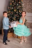 Happy children brother and sister near the new year tree with a Christmas presents stock photo