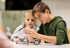 Happy children building robots at robotics school. Education, children, technology, science and people concept - happy boys building robots at robotics school Royalty Free Stock Photos